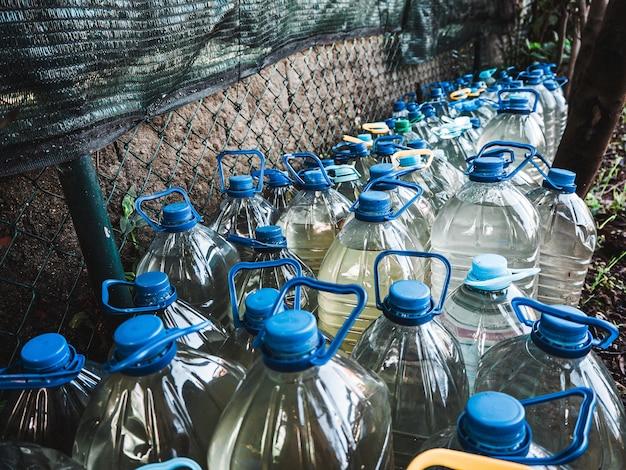庭の壁の前に水で満たされたペットボトルの数