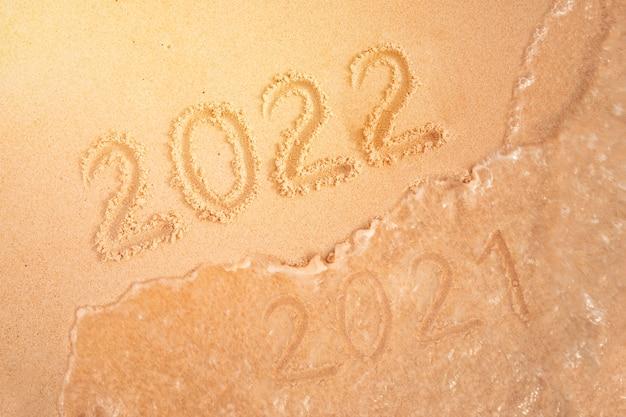 熱帯のビーチで、砂で書かれた新年の数。番号2021を2022に変更します。熱帯の島の年末年始。海の波が碑文2021を洗い流します。