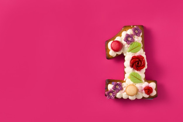 Number one cake decorated with flowers and cookies on pink surface copy space