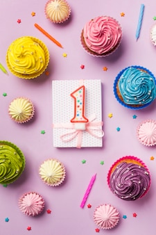 Number one candle on wrapped gift box with decorative muffins; aalaw and sprinkles on pink backdrop