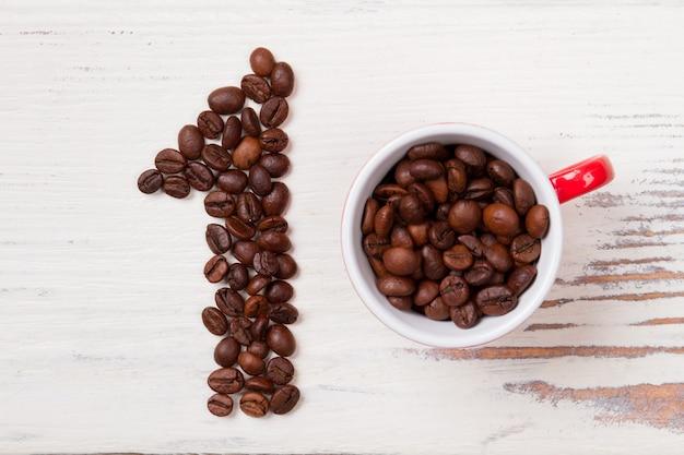 ナンバーワンのコーヒー。コーヒーの粒が入った平らな横たわったカップ。白い木に豆を使ったナンバーワン。