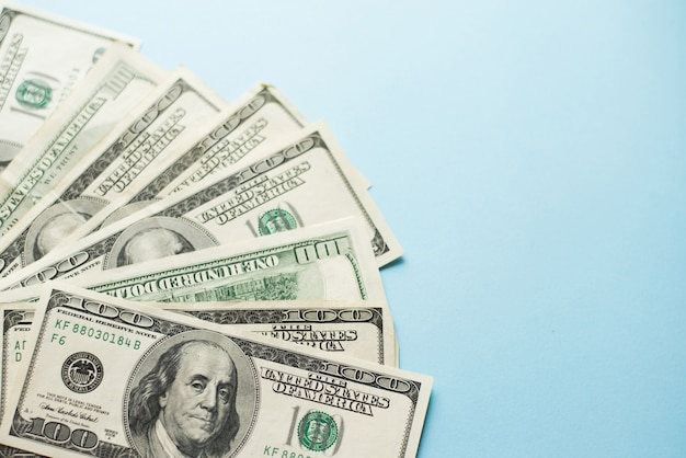A number of one hundred us dollar notes on light blue background.