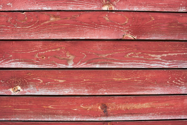 A number of  planks with cracked red paint