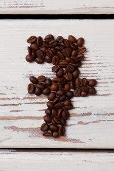 焙煎したコーヒー豆の七番。白い木の板。縦長の画像。