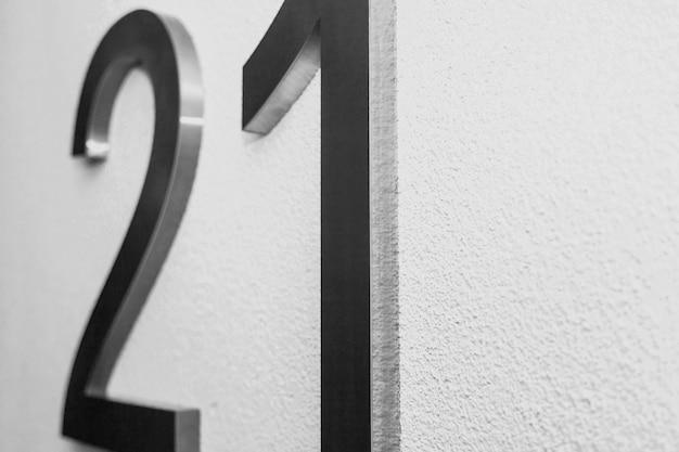 2021년을 상징하는 질감 밝은 벽의 21번. 질감 있는 표면 흰색 그라데이션 배경의 크롬 숫자 21입니다. 숫자 2와 1이 있는 흑백 배경. 복사 공간