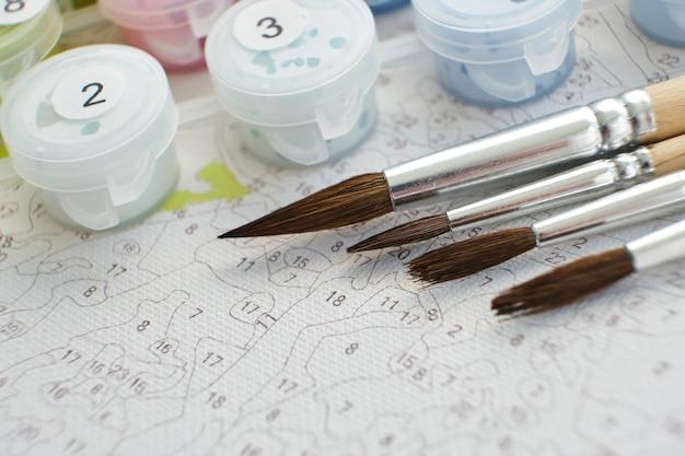 絵の具とブラシが付いた番号付きのコンテナがキャンバスの背景にあります。クリエイティブなレジャー活動