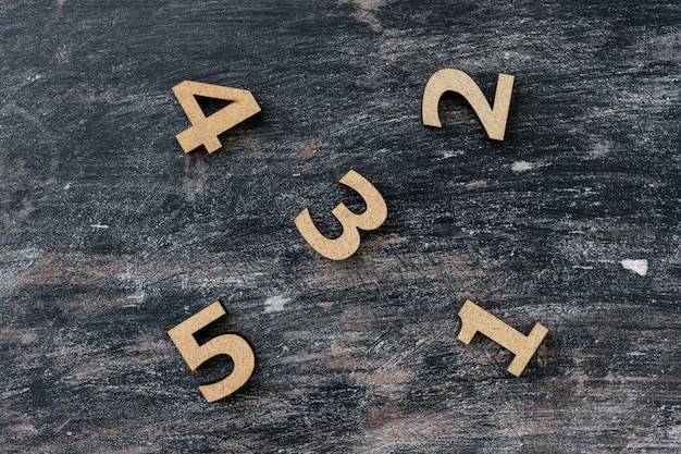 Numbers 1, 2, 3, 4, 5 on a dark vintage wooden table.