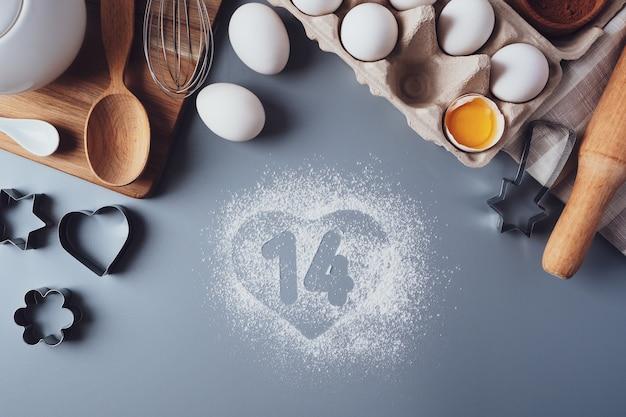 14番と小麦粉の心臓部。バレンタインデーのコンセプト。バレンタインデーのための自家製クッキーを作る、フラットレイ、トップビュー。灰色の背景で焼くための材料。