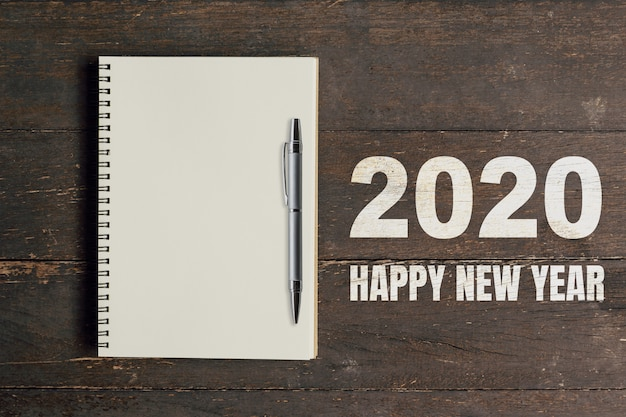 Numbers 2020 for happy new year and blank notebook with pen