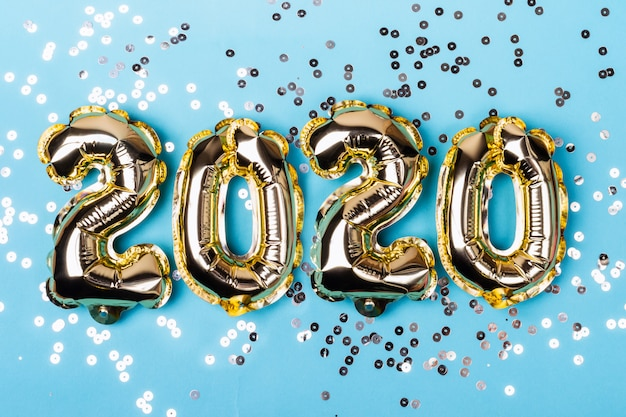 Numbers 2020 made from foil balloons on blue sparkles background