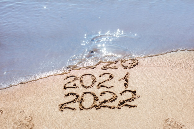 The numbers 2021, 2022 are drawn on the sand and washed away by the wave, the symbol of the new year, the change of the year, the calendar
