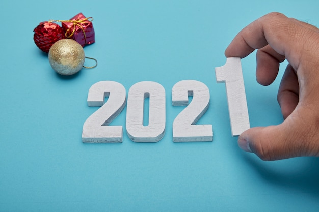 Цифры 2021 и рука на пастельно-синем фоне на новый год