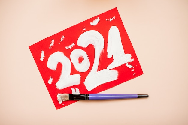 The numbers 2021 are written in white paint on a red sheet of paper. new year. christmas