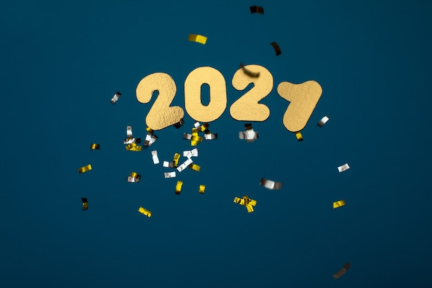 Numbers 2021 on a blue background with glasses of champagne and candy