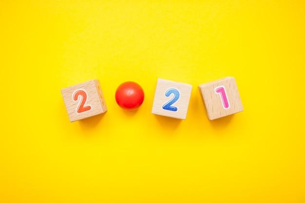 밝은 노란색 배경에 어린이 큐브의 숫자 2021. 새해 크리스마스