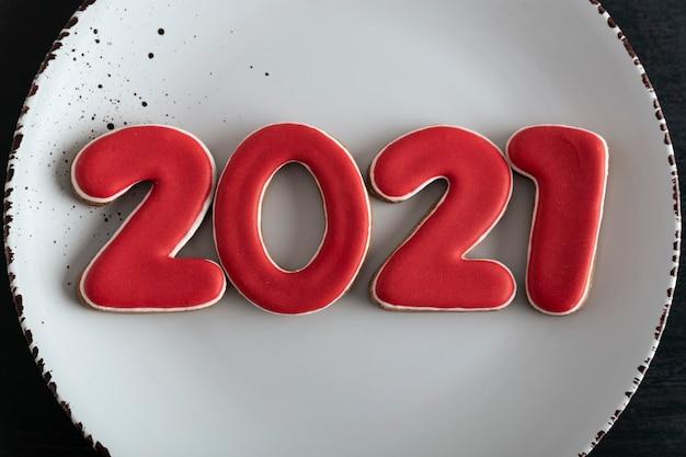 Цифры 2021 из пряников 2021 на белой тарелке, крупным планом. новогодняя концепция.