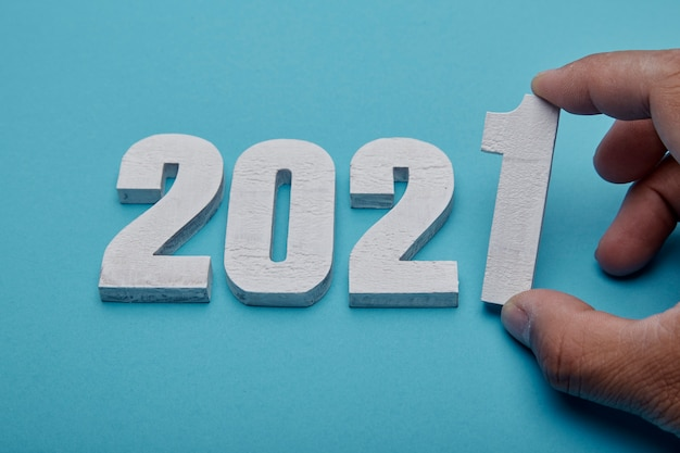 Numbers 2021 and hand on pastel blue background for new year