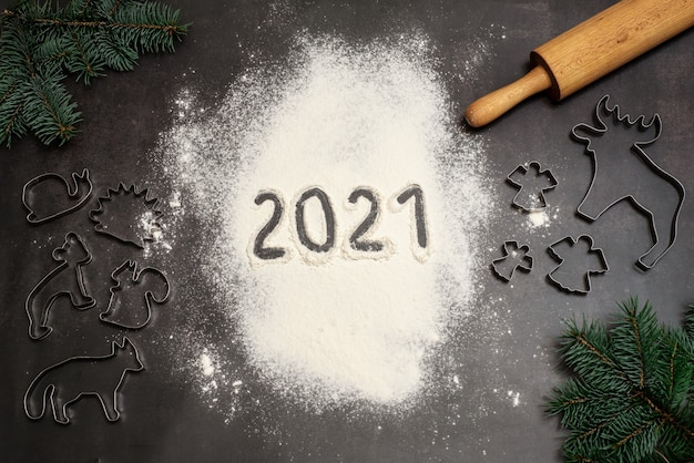 Numbers 2021 handwritten on flour with christmas cookie cutters, rolling pin and pine branches