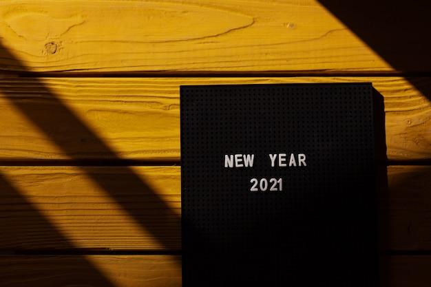 太陽の光と黄色の木の背景の文字盤の番号2021。新しい2021年のコンセプト、上面図。