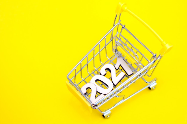 The numbers 2021 in a supermarket toy cart on a yellow background.