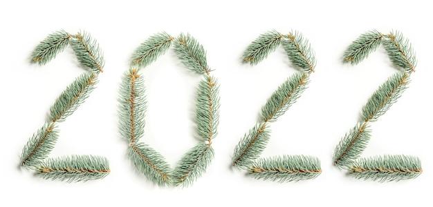 白い背景で隔離のクリスマスツリーの枝からレイアウトされた番号2022。新年のシンボル。