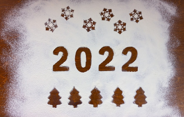 Numbers 2022, snowflakes and christmas trees drawn on flour on a wooden table.