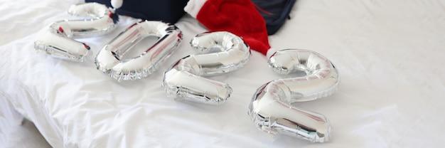 サンタクロースの帽子をかぶったものが入った数字と集められたスーツケースがベッドに横たわっています