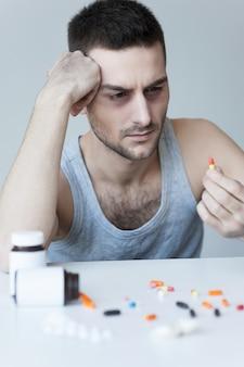 그의 고통을 마비. 테이블에 더 많은 알약이 놓여 있는 동안 테이블에 앉아 손에 있는 알약을 보고 좌절한 젊은 남자