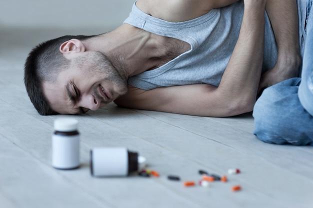 그의 고통을 마비. 젊은 남자가 바닥에 누워 약이 든 병이 그 근처에 놓여 있는 동안 뱃속에 손을 잡고