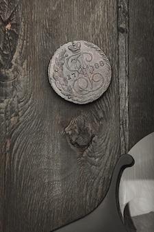 Нумизматика. античная коллекционная монета и лупа на старом деревянном столе. темный фон. вид сверху.