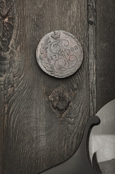 Numismatics. antique collectible coin and magnifier on an old wooden table. dark background. top view.
