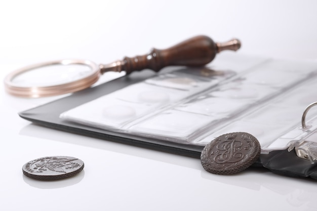 Нумизматика. старые коллекционные монеты и увеличительное стекло на столе. светлый фон.