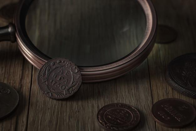 고전학. 나무 테이블에 구리로 만든 오래 된 소장 동전. 나무 테이블에 금으로 만든 오래 된 소장 동전.