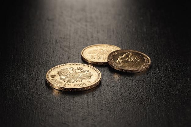 Нумизматика. старые коллекционные монеты из золота на деревянном столе. нумизматика. старые коллекционные монеты из золота на деревянном столе.