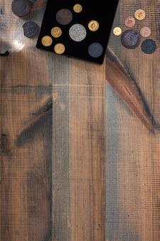 貨幣学。木製のテーブルに銀、金、銅で作られた古い収集コイン。上面図。あなたのテキストのスペースをコピーします。