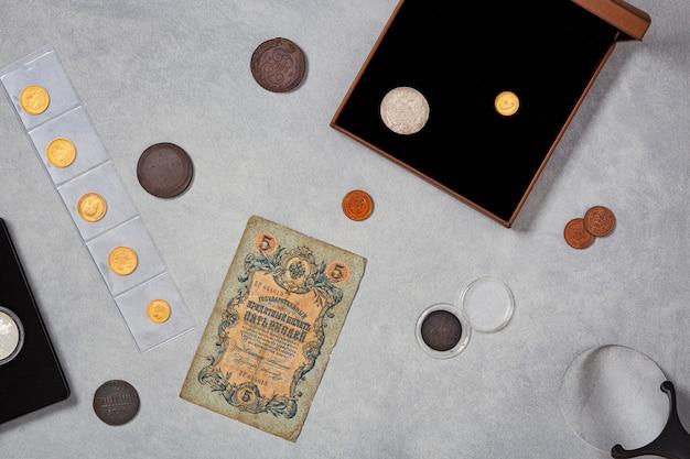 貨幣学。木製のテーブルに銀、金、銅で作られた古い収集コイン。上面図。