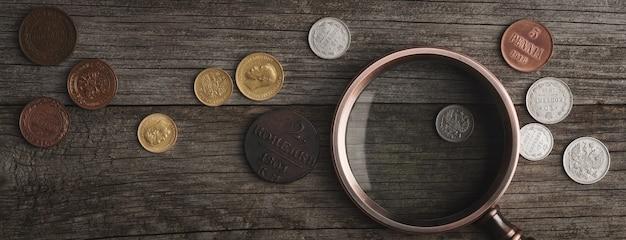 고전학. 나무 테이블에 실버로 만든 오래 된 소장 동전. 특수 장갑의 수집가가 오래된 동전을 들고 있습니다. 평면도.