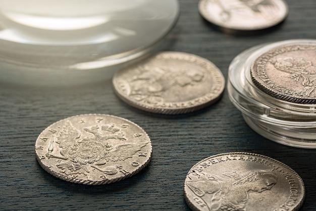 Нумизматика. старые коллекционные монеты из серебра на деревянном столе. нумизматика. старые коллекционные монеты из золота на деревянном столе.