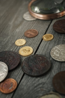 Нумизматика. старые коллекционные монеты из серебра, золота и меди на столе. вид сверху.
