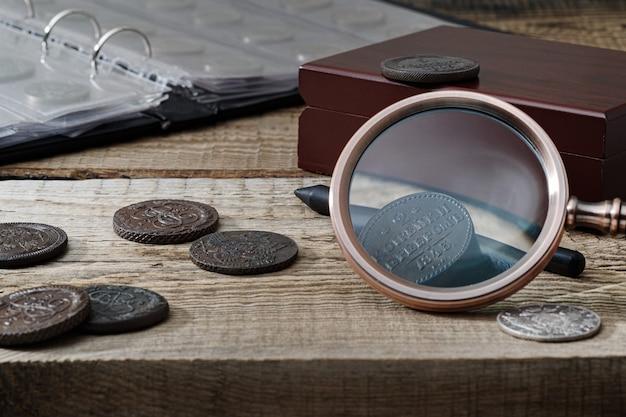 Нумизматика. старые коллекционные монеты на деревянном столе. темный фон.