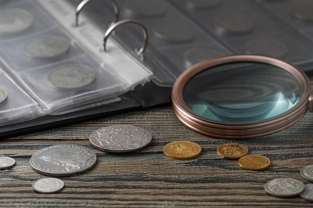 Нумизматика. старые коллекционные монеты на деревянном столе. нумизматика. старые коллекционные монеты из золота на деревянном столе.