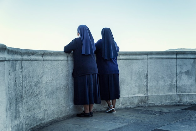 Nuns in black dresses look at the sea from the balcony of notre dame in marseille. back view.