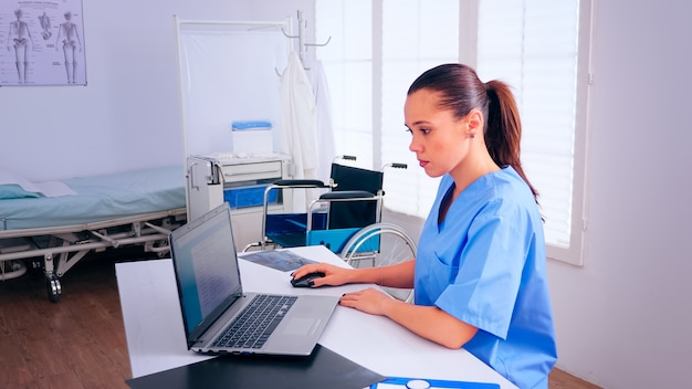 Nurse analysing list of patients on laptop, therapist typing on computer consult patient online. medical physician in medicine uniform writing list of consulted, diagnosed patients, making research.