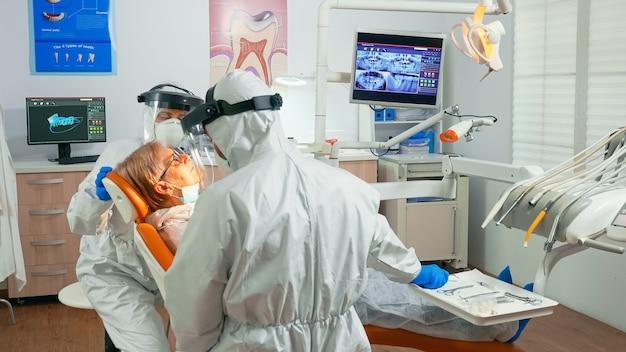 コロナウイルスパンデミック治療中の高齢患者の歯科ユニットで働く保護スーツの看護師と医師。つなぎ服、フェイスシールド、マスク、手袋を着用したアシスタントおよび歯科矯正医。