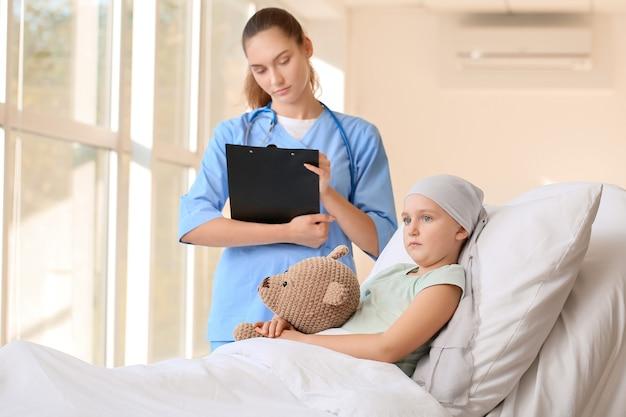 병원에서 화학 요법의 과정을 받고 간호사와 어린 소녀