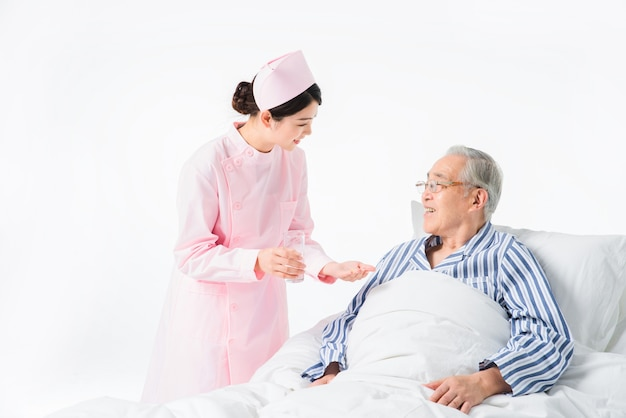 Медсестра и старик принимают лекарство