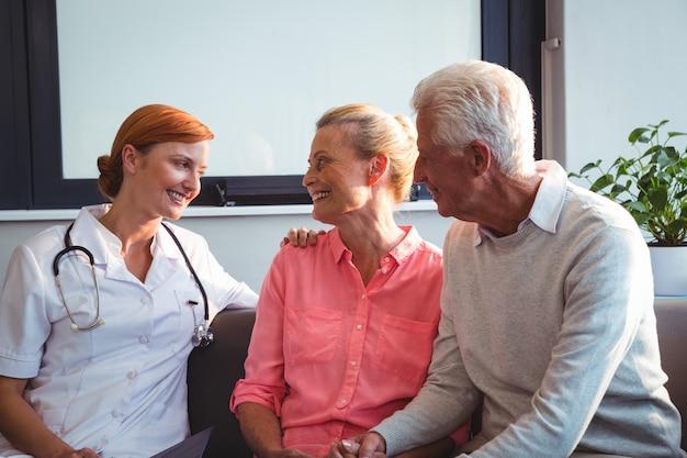 ソファに座っている看護師と年配のカップル