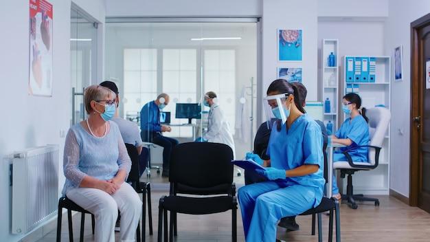 간호사와 노인 환자가 대기실에서 병원 진찰실로 가고 있습니다. 의사는 사무실에서 상담을 위해 늙은 여자를 초대합니다. 코로나바이러스에 대한 마스크 착용.