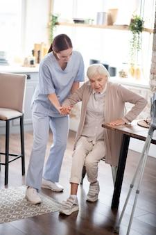 Медсестра помогает пожилой женщине делать шаги после операции