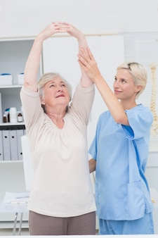 Nurse assisting female patient in raising arms